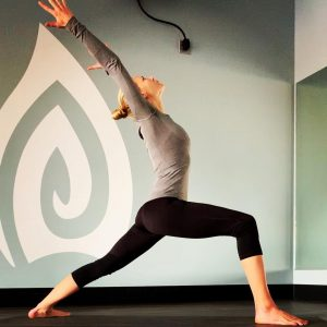 yoga pose with authentic yoga studio logo in background